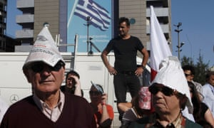 People wear paper hats as they take part in a march by members of Greece's Communist party during a 24-hour labour strike in Athens October 18, 2012.