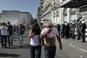 Greece protests: Protesters cover their faces and march amid tear gas