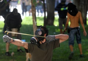 Greece protests: A demonstrator uses a sling shot against riot policemen