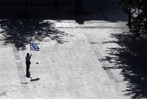 Greece protests: A elderly protester holds a Greek flag in a deserted Syntagma square