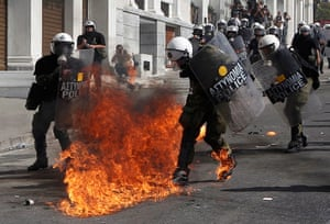 Greece protests: Flames from a molotov cocktail burn on the boots of Greek riot police