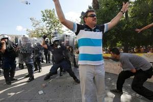 Greece protests: A man reacts as riot police and a demonstrator clash behind him