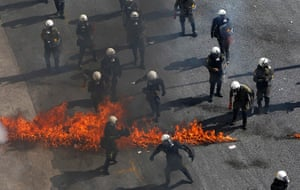 Greece protests: Greek riot police try to avoid flames from a molotov cocktail