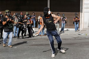 Greece protests: Press photographers cirle a protester as he throws a rock