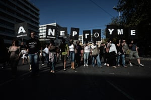 Greece protest update: Demonstrators hold banners reading 'we work as unemployees' during a rally