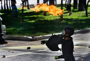 Greece protest update: A protester throws a petrol bomb at riot police during a violent clashes