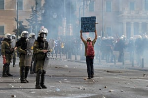 Greece protest update: A man holds a placard in front of riot police