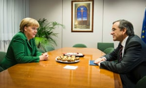 Greece's Prime Minister Antonis Samaras (R) talks with Germany's Chancellor Angela Merkel in the room of the Greek delegation during a European Union leaders summit in Brussels October 19, 2012.