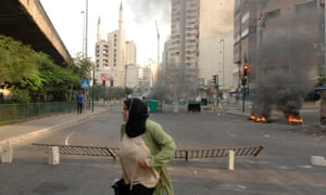 A woman runs for cover near burning tyres and barricades during clashes between members of the Lebanese army and Sunni Muslim gunmen in Beirut on 22 October after a night of tension following the funeral of an intelligence official killed by a car bomb