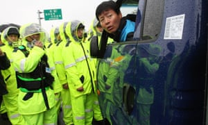 Police officers block an activist in a car carrying anti-North Korea leaflets in Paju near the demilitarized zone, South Korea.