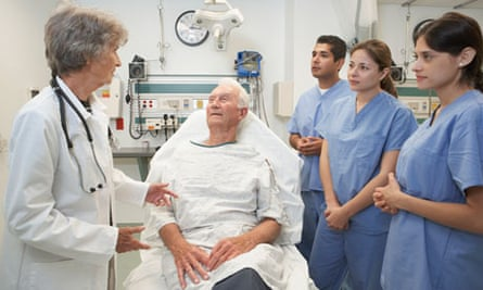A senior female doctor in a hospital talking to a patient while medical students listen.