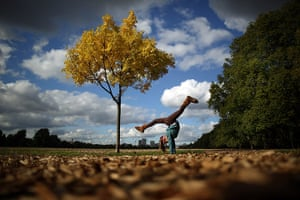 Autumn colours: A girl a handstand under a yellowing tree in Hyde Park in London