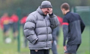 Manchester United manager Sir Alex Ferguson smiles despite the weather during a wet training session.