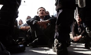 Opposition party leader Albin Kurti sits in front of Kosovo police during an anti-Serbia protest in Kosovo's capital Pristina. Kosovo police in riot gear fired teargas and used batons to disperse dozens of ethnic Albanians protesting a meeting between the prime minister, Hashim Thaci, and Serbian leader Ivica Dacic