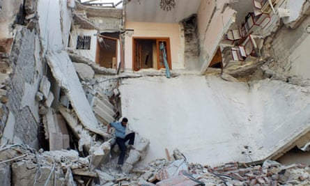 A Syrian man makes his way through the rubble of a building in Homs