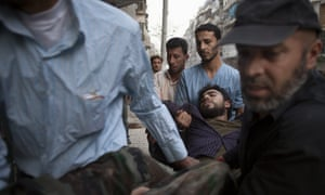 A wounded Syrian rebel is rushed to a clinic after being shot by a government sniper in the northern city of Aleppo.