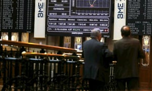 Two men watch a screen displaying a chart with the development of the Spanish index IBEX 35 at Madrid's Stock Exchange Market, in Madrid, Spain, 22 October 2012.