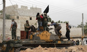 Marking the spoils or war: Members of the Free Syrian Army raise a black flag over a tank that belonged to pro-government forces after they took over the site from them early Monday in Salqin city in Idlib. Photograph: Asmaa Waguih/Reuters