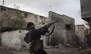 A Syrian rebel fires towards an army position in the Karm al-Jabal district of the northern city of Aleppo on Monday.