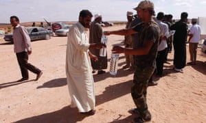 A security official gives water to a man fleeing the fighting in Bani Walid, at the Om Rishrash checkpoint in Tarhouna on Monday.  Families fleeing violence in the besieged Libyan city of Bani Walid said there were shortages of food and water and the city's hospital was under fire as militias loyal to the government shelled the former stronghold of Muammar Gaddafi.