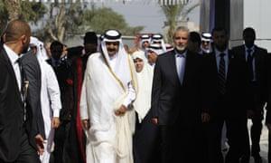 Qatari emir Sheikh Hamad bin Khalifa al-Thani and Gaza's Hamas prime minister Ismail Haniya attend a welcome ceremony at the Rafah border crossing with Egypt
