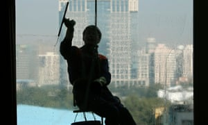 A window cleaner squeegees a window of an apartment building at a residential area in central Beijing.