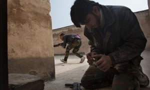 A rebel fighter loads his weapon while his companion fires his Kalashnikov on the rooftop of house during fighting against Syrian government forces in the Bab el-Adid district in Aleppo.