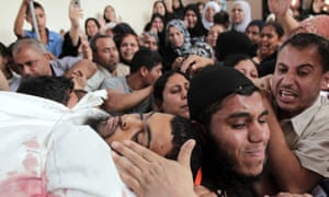 Palestinian mourners carry the body of Mohamed al-Shikh during his funeral in Rafah, southern Gaza.  Palestinians fired more than 40 rockets from the Gaza Strip into Israel injuring three people, while Israeli air strikes on the territory killed three militants, police and medics said.