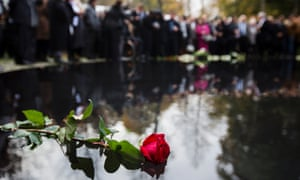 People lay flowers during the opening of the Memorial to the Sinti and Roma of Europe murdered under National Socialism in Berlin.