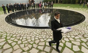 And here Messina Weiss, 12, great grand-daughter of Holocaust survivor Gertrud Rocher, carries a flower past the Memorial.