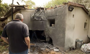 An Israeli man inspects the damage to hi