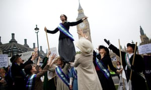 Feminist activists dressed as The Suffragettes protest at Parliament Square for women's rights and equality in London.