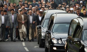 The husband of Sabah Usmani, Dr Abdul Shakoor 5th from left, members of the Muslim community and friends and family of Sabah Usmani and her five children, who were killed in a house fire, follow the funeral cortege to the crematorium after a service of prayer in Harlow, England.