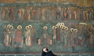Er, where's my halo? A man walks by the painted wall of the Romanian patriarchy after attending prayers in Bucharest, Romania.