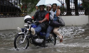 People ride a motorbike in heavy rain due to the passing of hurricane 'Sandy' in Santo Domingo, Dominican Republic, last night, 24 October.