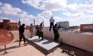 Libyan militia fighters aligned with the defence ministry celebrate on top of a building in the centre of the former Gaddafi stronghold of Bani Walid October 24, 2012. The fighters said they had taken control of the town on Wednesday but there were still some pockets of resistance.