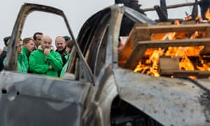 A car burns as workers block the main gate of the Ford plant in Genk, Belgium. Ford Motor Co. announced Wednesday it planned to close the car plant in eastern Belgium.