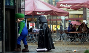 Tourists laugh as street artists dressed up as Darth Vader and Super Mario enter a subway station at the Brandenburg Gate in Berlin.