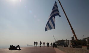 A giant Greek flag is raised by a crane in the port of Thessaloniki