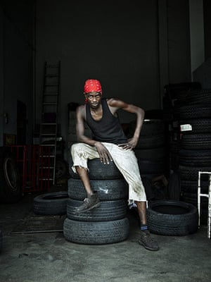 Jamaican Musicians: Tyre fitter Philip Ricardo Carr in desert boots, Crossroads, Kingston 2011