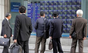 People look at an electronic stock board of a securities firm in Tokyo, Friday, Oct. 26, 2012.