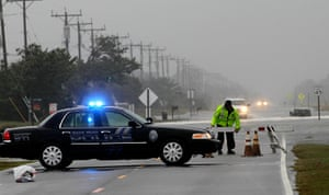 Hurricane Sandy : A police officer sets up a road block on South Oregon Inlet Road