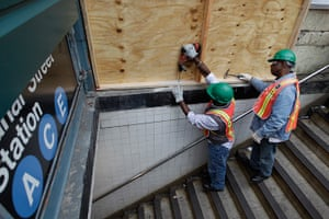 Hurricane Sandy : Workers cover a station entrance with plywood to help prevent flooding