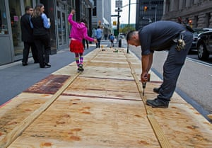 Hurricane Sandy : A maintenance worker attaches plywood to a sidewalk grate
