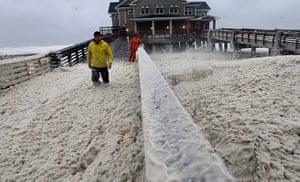 Hurricane Sandy : A news crew wades through sea foam blown onto Jeanette's Pier