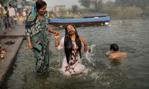 Another watery scene: Indian Hindu devotee takes a holy dip in  the Yamuna River on Sharad Purnima, an auspicious day for the new moon in the autumn, in New Delhi, India.