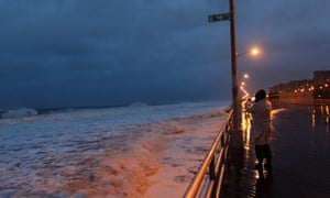 A woman takes a photo at Beach 98th street on the boardwalk at Rockaway beach in Queens, New York.