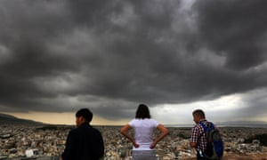 Tourists view Athens from the top of the ancient hill of the Acropolis during a rainy day in the city.