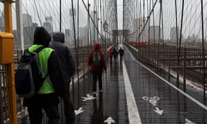 Here people walk across the Brooklyn Bridge as the public transport system has been shut down in New York.