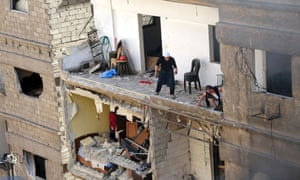 In this photo released by the Syrian official news agency SANA, Syrian citizens are seen on a damaged building that was hit by a car bomb, in the Jaramana neighbourhood, in Damascus.